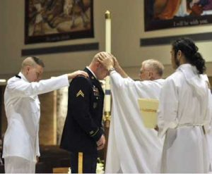 Ensign Anthony Lezcano, USN, a co-sponsored seminarian, places his hand on the shoulder of Bradley Lewis who is being received into full communion with the Catholic Church at St. Charles Borromeo Catholic Church in Tacoma, WA at the Easter Vigil Mass on 7 Apr 12.